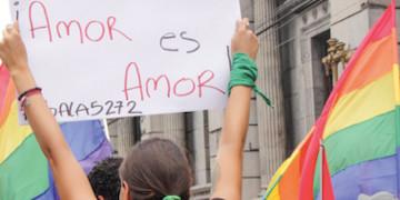 """Person hält ein Schild mit der Aufschrift """"Amor es Amor"""""""