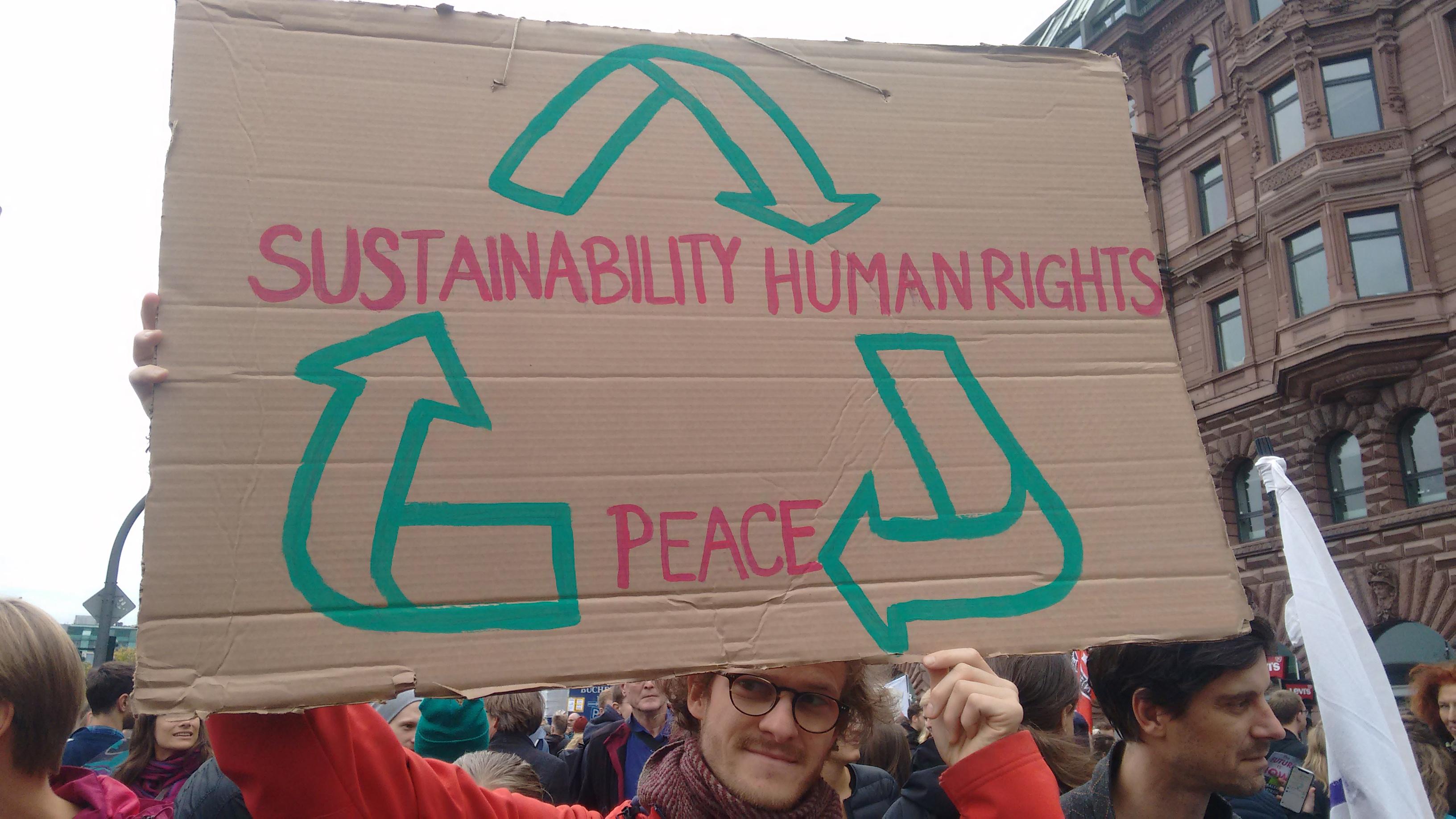 """Person mit Schild mit der Aufschrift """"Sustainability > Human Rights > Peace"""" auf einer Demonstration"""